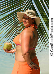tropical beach woman - voluptuous woman holding coconut with...
