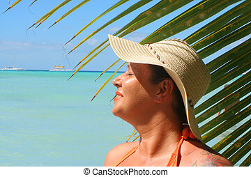 tropical beach woman - voluptuous woman soaks up the sun...