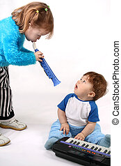 Duo - Small boy plays with the electronic piano. Girl plays...