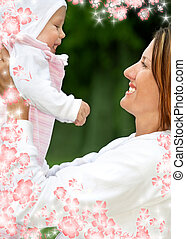 happy mother with baby and flowers - outdoor picture of...