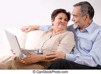 Senior couple on laptop. Concept may be is shopping in...