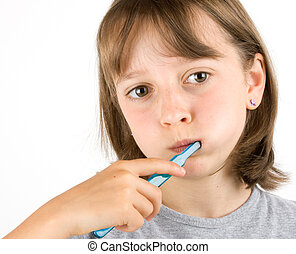 Dental Health - Girl brushing her teeth against a white...