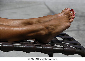 Tanning Toes - Legs and feet of a woman getting a tan on a...