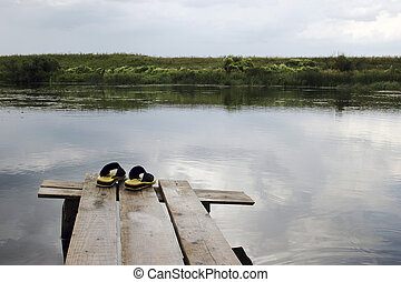 Yellow rubber slippers on wooden bridge