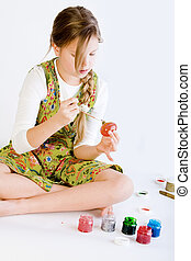 Young girl painting her easter eggs - Studio portrait of a...