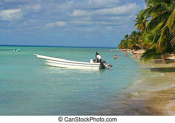 Caribbean shoreline - Men getting motorboat started on a...