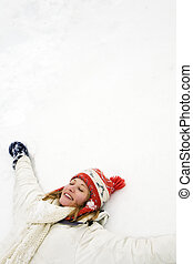 winter scene: blond girl laying down on the snow Copy space...