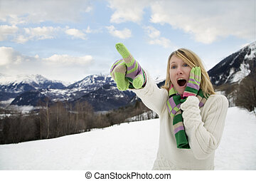 winter scene: astonished woman pointing 1 finger up in the...