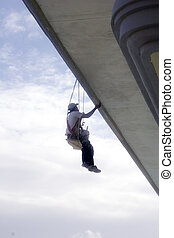 Hanging From Roof - A painter in a harness hanging from the...
