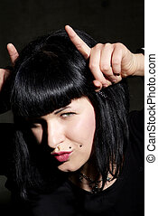 playful woman - a woman with black hair and piercing shows...
