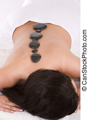 Hotstone massage - Woman lying on a massage table getting a...