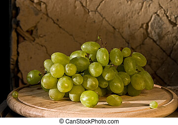 grapes - branch of green grapes on the wooden board