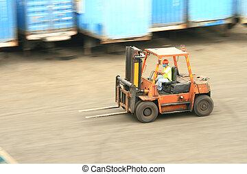 forklift in motion - orange forklift in motion at a ship...