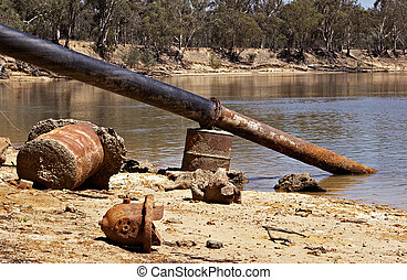 river pollution - old rusty metal and pipe going into the...