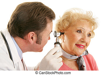 Senior Lady Gets Checkup - Doctor using otoscope to look...