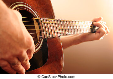 Person playing a guitar - Hands of a person playing an...