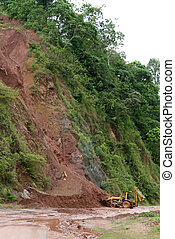 Highway Mudslide - A backhoe moves dirt and mud from a...