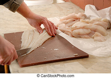 cutting fish - fishmonger preparing fillets of fish - close...