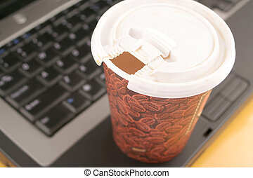 office coffee - a cup of coffee to go on top of laptop
