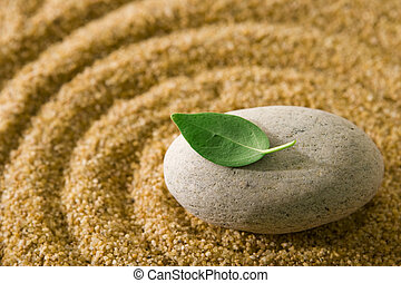 Zen stone - Raked sand and stone with a green leaf on top