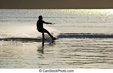 sunset waterskier dazzling light - sunset waterskiing...