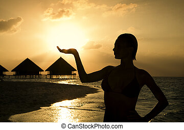 tropical beach: beautiful girl holding the sun in her hands