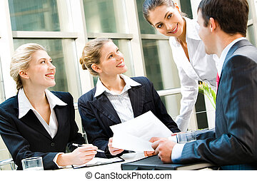 Working team - Team of four business people discussing an...