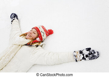 winter scene: blond girl laying down on the snow. Copy space...