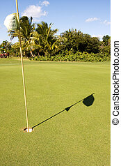shadow flagpole - golf flagpole in hole with shadow on green