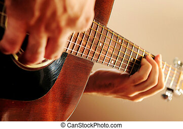 Man playing a guitar - Hands of a person playing an acoustic...