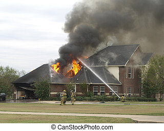 Firefighters and a house fire - Firefighters extinguishing a...