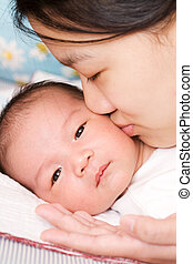 Mother and baby - An asian mother kissing her baby boy