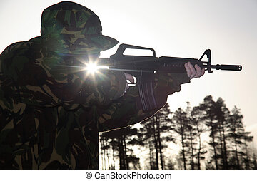 Soldier, his Rifle and the Sun - A soldier standing up...