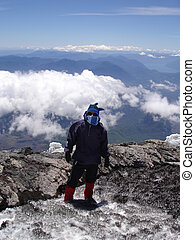 Mountain Climber - A young man on his way up a volcano in...