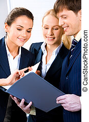 Business meeting - Team of three people discussing an...