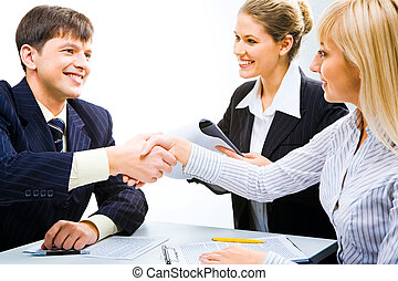 Handshake - Business partners shaking hands and looking at...