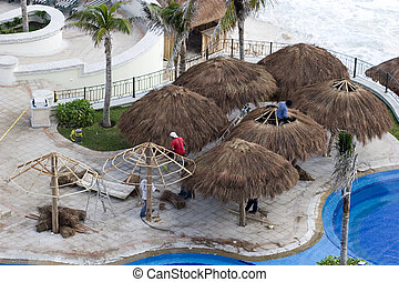 Straw Roof Thatchers - Workers building straw thatch roofed...