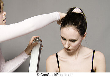 The hairstylist - a model portrait in the studio getting her...