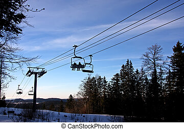Cable car - ski cable car at sunset with trees in the...