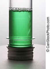 Test tubes - Test tube with a green liquid on a white...