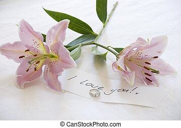 Lillies and love - two beautiful lillies lie on the bed by a...