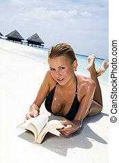 tropical beach: girl reading a book on the seashore