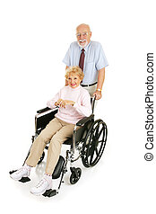 Senior Cares for Spouse - Senior man pushing his wife in...