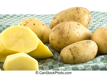 Peeled potatoes - peeled and unpeeled potatoes on a green...