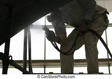 man painting - close-up view of one man bending over holding...