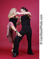 Tango - Beautiful blond and brunet dancing tango on red...