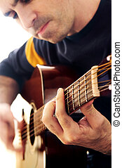 Man playing a guitar - Man playing a musical instrument...
