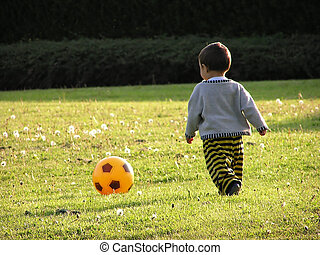 boy learning soccer - child taking his first soccer lessons...