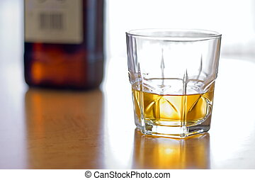 Glass of whiskey - Glass of yellow whiskey and brown bottle...