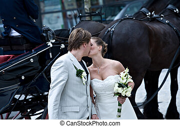 We and the horses - Bride and groom kissing standing in...